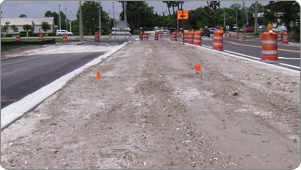 Gravel bed for road construction with traffic barrels and cones. Detour sign and traffic light up ahead..